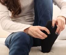 【脚・ひざ】ソファーに座って足をマッサージする女性