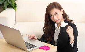 【生活】パソコンをしながら笑顔のビジネススーツ女性
